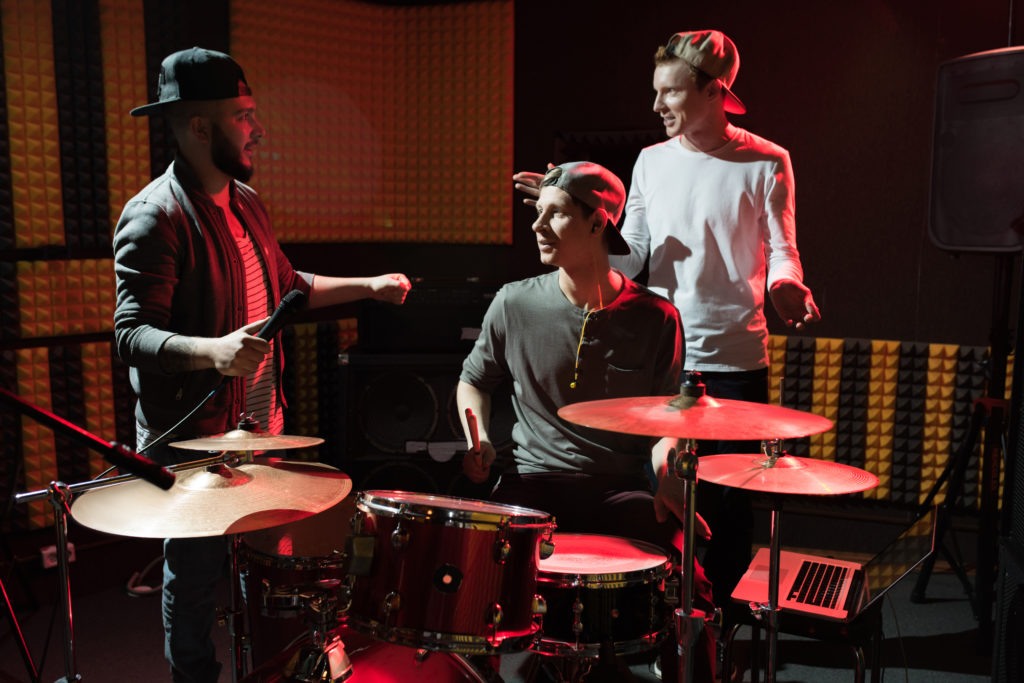 Portrait of modern hip-hop band rehearsing in recording studio lit by red lights while making new album