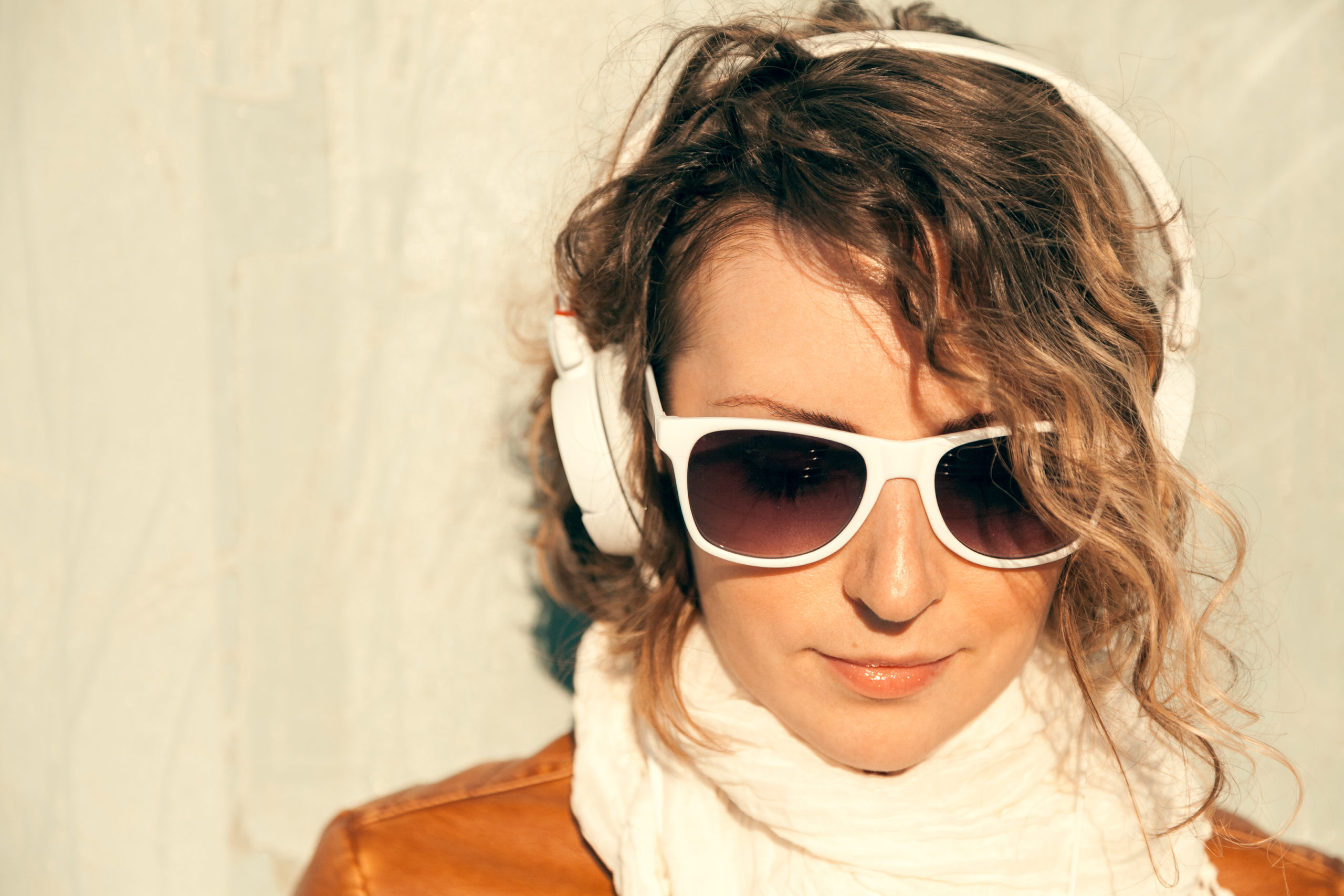 Beautiful young woman in a sunglasses and headphones listening music near the wall