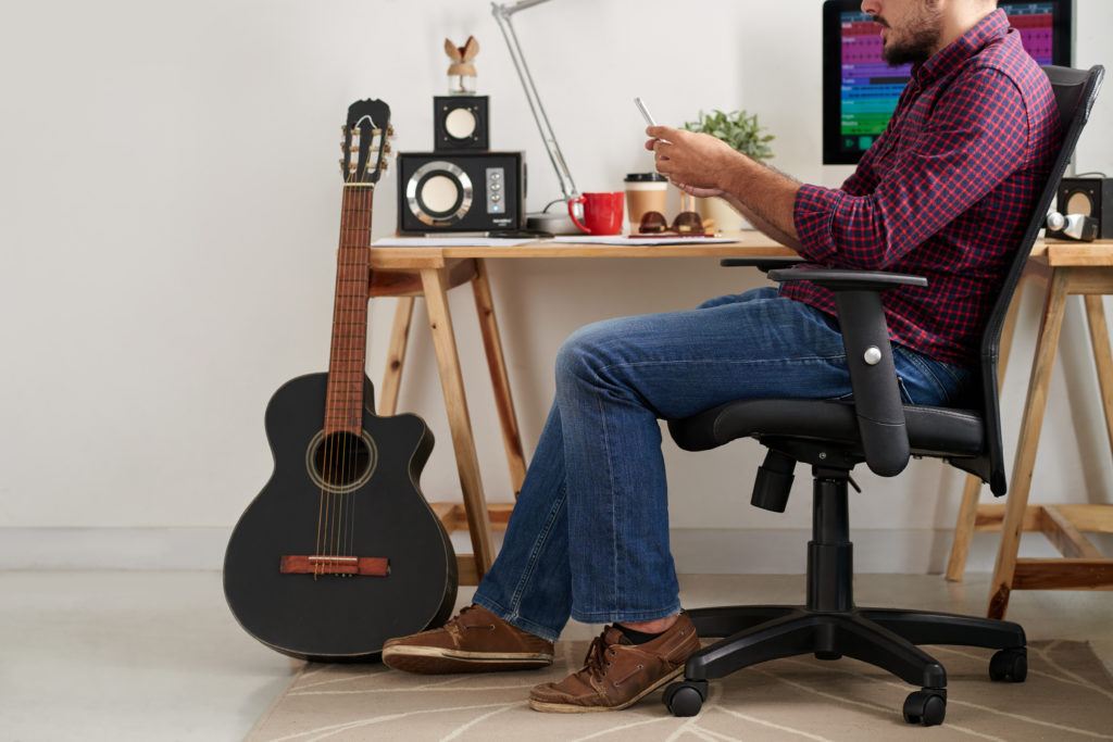 Young casual man sitting on chair near the table with computer and guitar and using his smartphone while working at sound studio