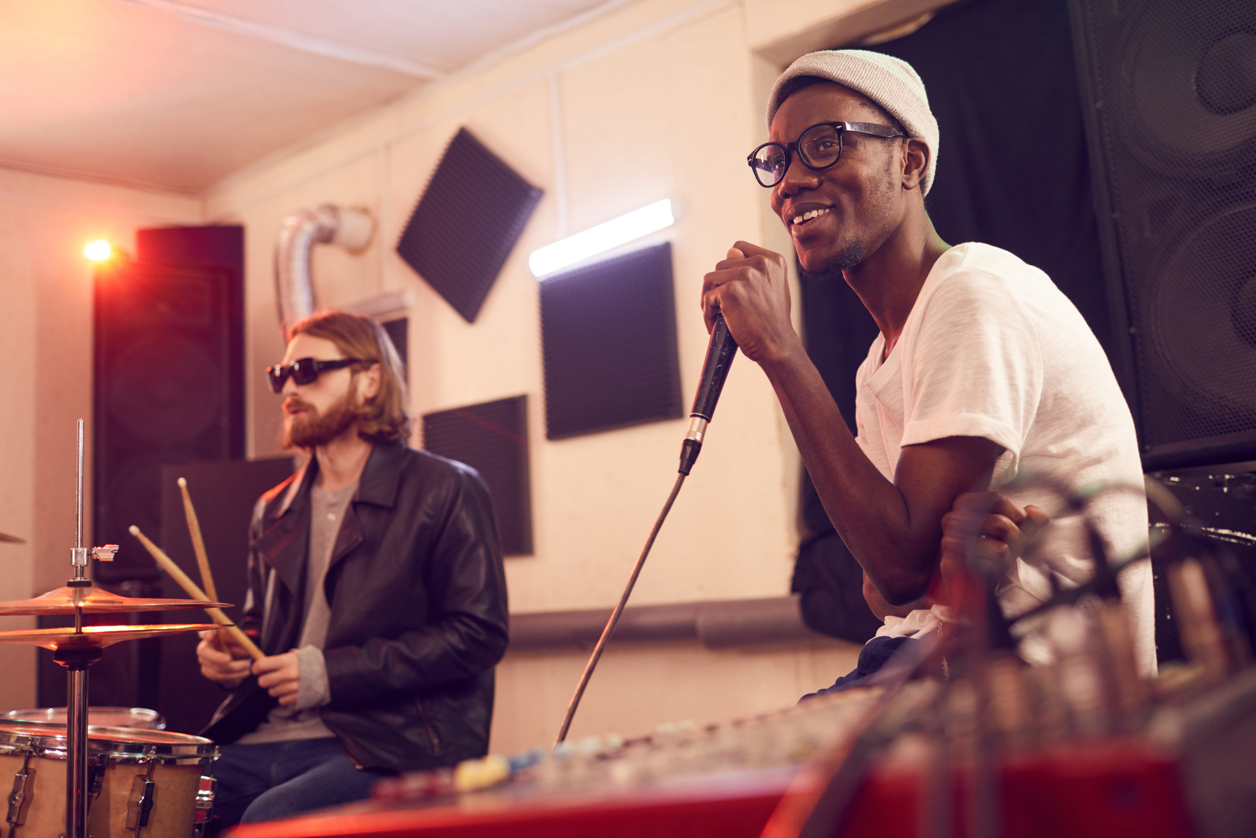 Portrait of contemporary African-American man singing to microphone and smiling happily during rehearsal or concert in music studio, copy space